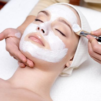 9244711 - beautiful young woman receiving facial mask at beauty salon - indoors