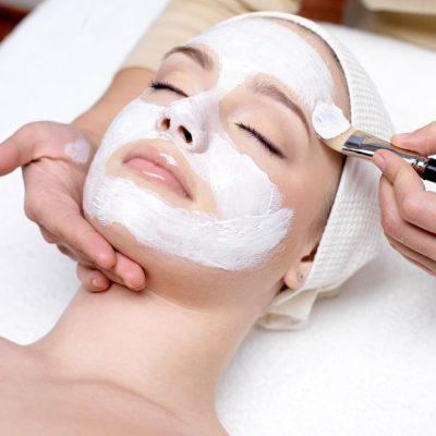 9244711 - beautiful young woman receiving facial mask at beauty salon - indoors